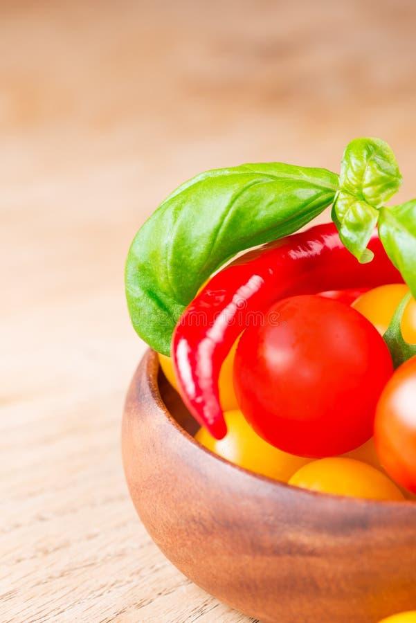 La albahaca hojea con los tomates de cereza y la pimienta de chile imagen de archivo