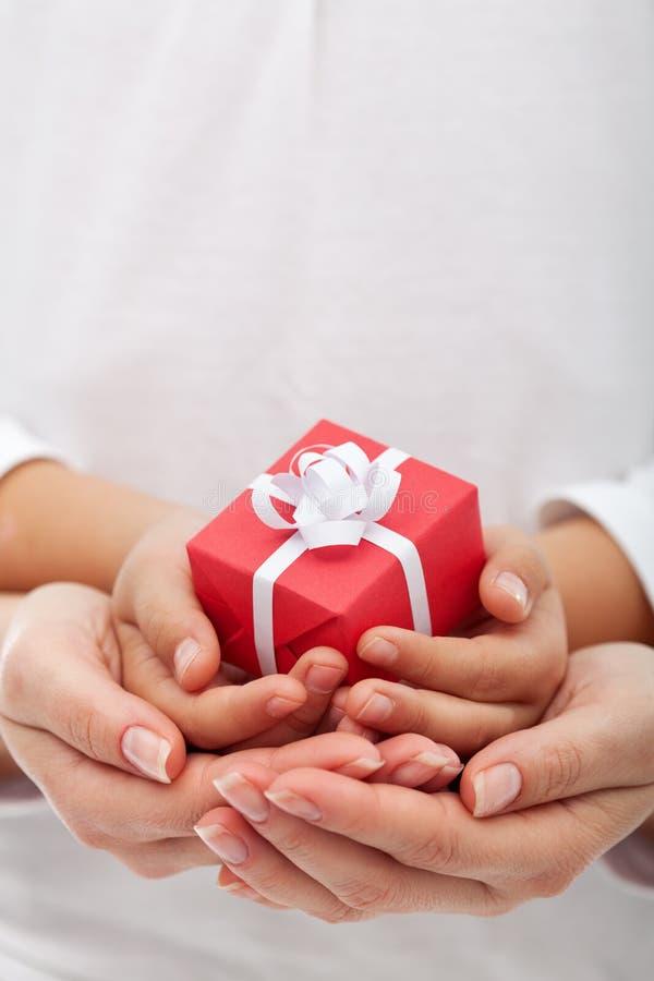 La alegría del donante - pequeña caja de regalo en manos de la mujer y del niño fotografía de archivo libre de regalías