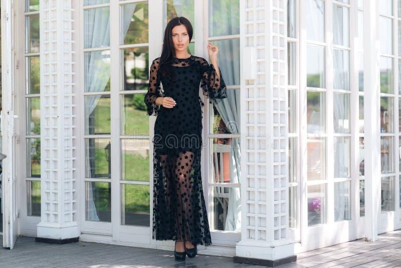 La alta muchacha europea atractiva delgada en un vestido negro apretado costoso sale del restaurante en la calle Corrige oscurida fotografía de archivo libre de regalías