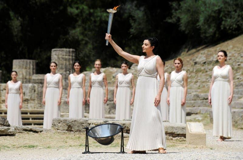 La alta sacerdotisa, la llama olímpica durante la iluminación de la antorcha cere imagen de archivo libre de regalías