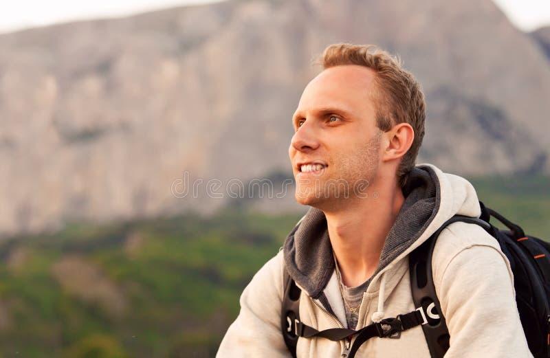 La altura del hombre joven goza después de subir en la montaña imagen de archivo