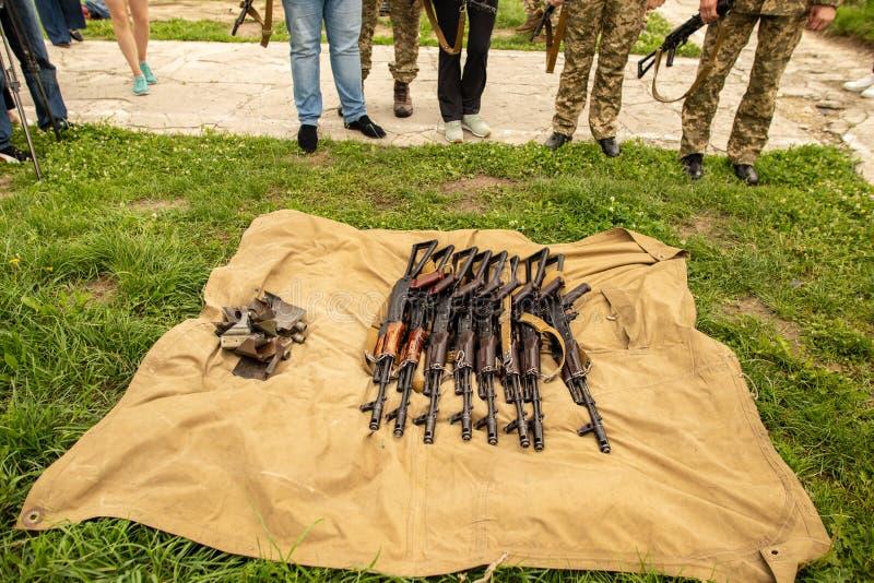 La ametralladora militar miente en la hierba seca en el campo imagen de archivo libre de regalías