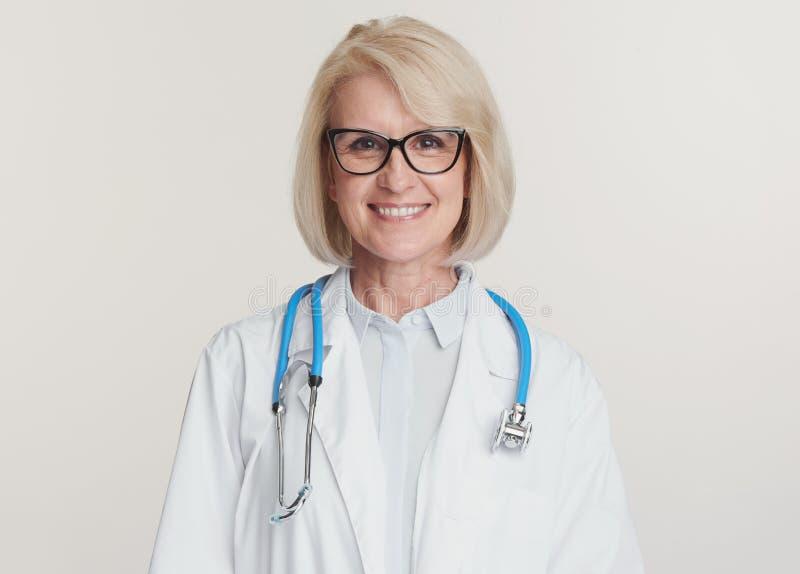 La amigable anciana doctora está sonriendo Aislado imagen de archivo