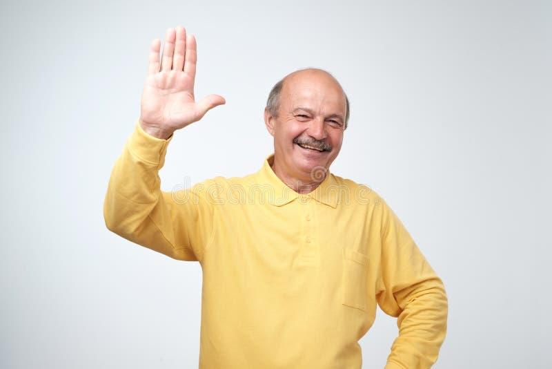 la Amistoso-mirada del pensionista europeo atractivo en camiseta amarilla renuncia la mano en hola gesto mientras que sonríe aleg foto de archivo libre de regalías