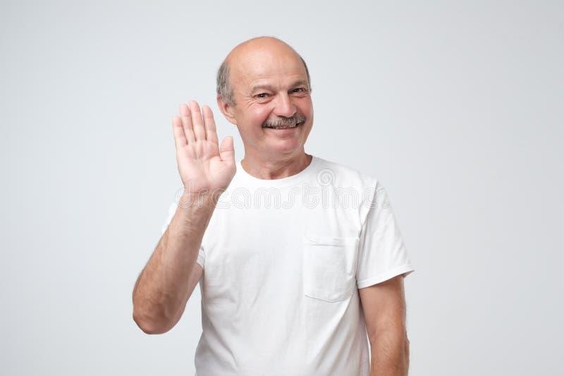 la Amistoso-mirada del pensionista europeo atractivo en la camiseta blanca renuncia la mano en hola gesto mientras que sonríe ale foto de archivo