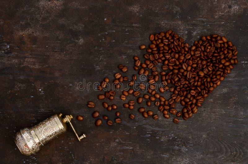 La amoladora manual del grano de café contiene los granos de café seleccionados, aislados foto de archivo