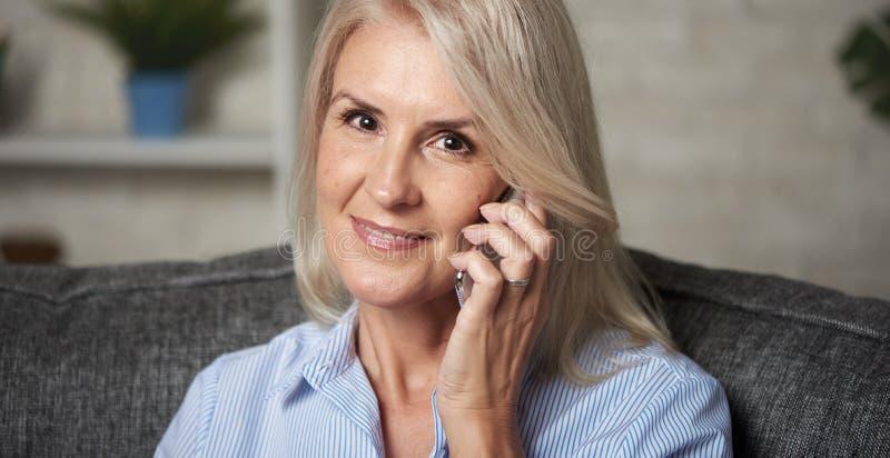La anciana está hablando por teléfono fotos de archivo libres de regalías