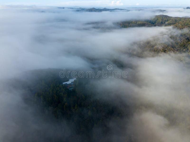 La antena, niebla de la mañana cubre las montañas fotos de archivo