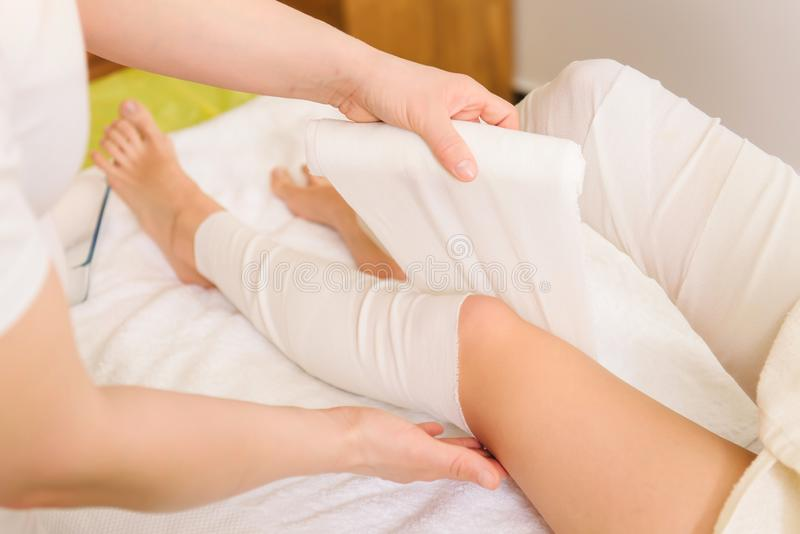 la Anti-cellulite avvolge la procedura per le gambe in un centro della stazione termale fotografia stock