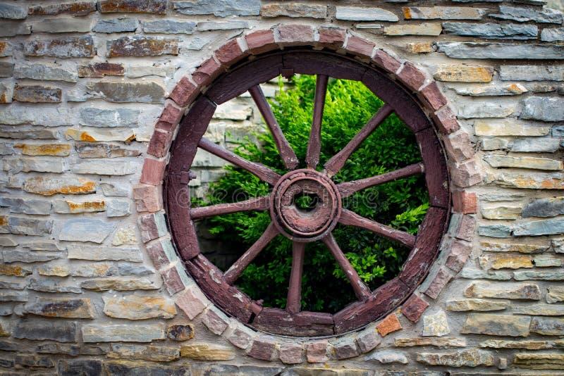 La antigüedad y el carro de madera resistido del carro ruedan adentro los BU de piedra viejos de la granja fotos de archivo libres de regalías