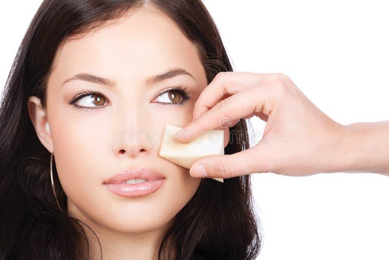 La aplicación bonita de la mujer compone con la esponja cosmética foto de archivo libre de regalías