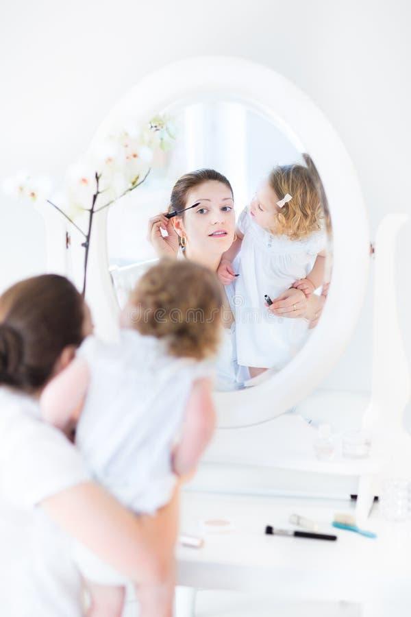 La aplicación de la mujer compone y su hija que lo mira imagen de archivo