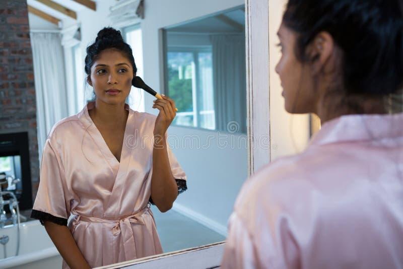La aplicación de la mujer se ruboriza con la reflexión en el espejo fotos de archivo libres de regalías