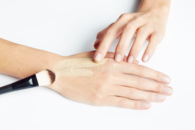 La aplicación de la mano de una mujer compone en la piel con el cepillo foto de archivo libre de regalías