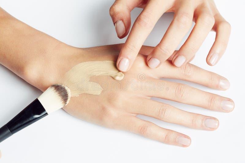 La aplicación de la mano de una mujer compone en la piel con el cepillo fotografía de archivo libre de regalías