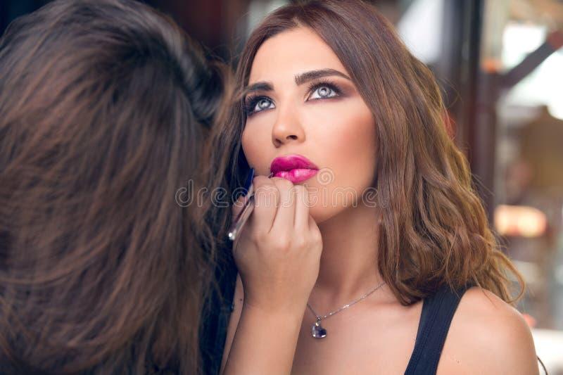 La aplicación del artista de maquillaje compone en modelo hermoso foto de archivo
