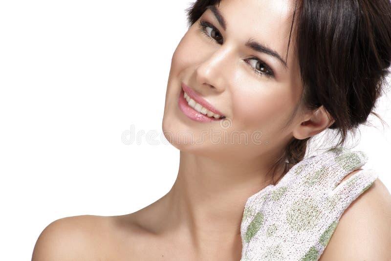 La aplicación hermosa de la mujer joven friega el guante en su piel perfecta foto de archivo
