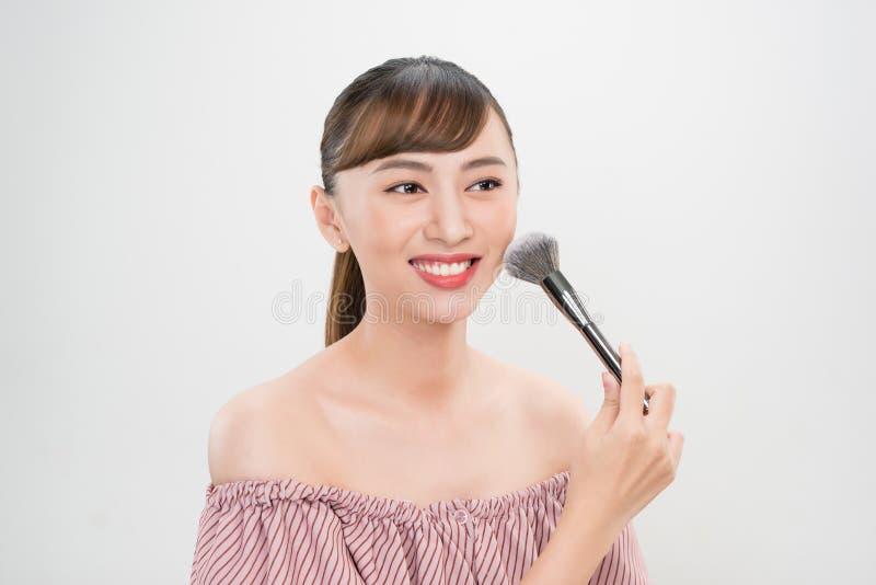 La aplicación sonriente hermosa de la muchacha floja se ruboriza con el cepillo cosmético imagen de archivo libre de regalías