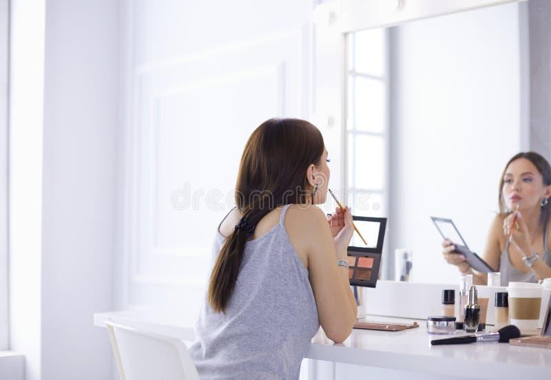 La aplicaci?n morena de la mujer compensa una fecha de igualaci?n delante de un espejo foto de archivo
