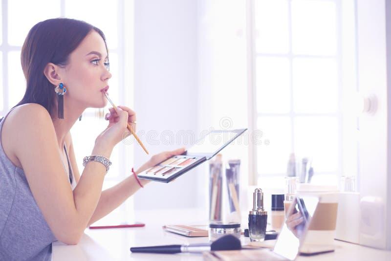 La aplicaci?n morena de la mujer compensa una fecha de igualaci?n delante de un espejo imagenes de archivo