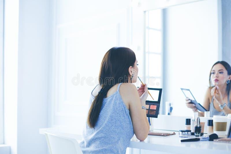 La aplicaci?n morena de la mujer compensa una fecha de igualaci?n delante de un espejo fotografía de archivo