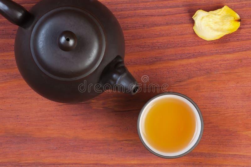 La arcilla esmaltó el cuenco con té preparado y la tetera de la arcilla en la tabla de madera roja adornó el pétalo color de rosa imagen de archivo