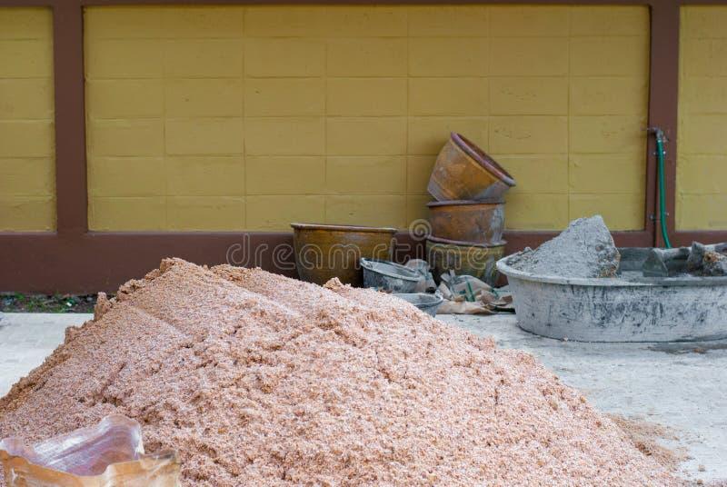 La arena de la construcción y la tina de mezcla concreta está en el piso listo imagenes de archivo