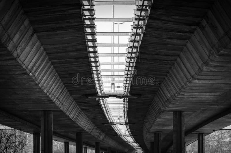 La arquitectura alinea bajo el puente con los polos concretos y refuerzo blanco y negro fotografía de archivo libre de regalías