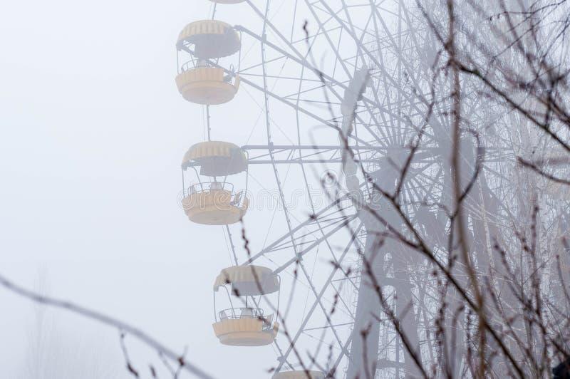 La atracción y los árboles de la noria del moho en invierno de niebla abandonaron el parque de atracciones en Pripyt, zona de Che fotos de archivo libres de regalías