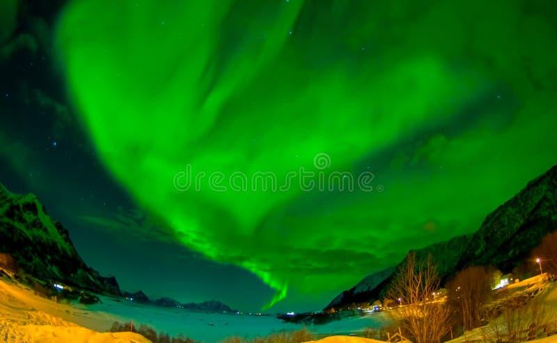 La aurora boreal brilla brillante y hermoso sobre picos y los lagos agudos de las montañas de Lofoten fotografía de archivo libre de regalías