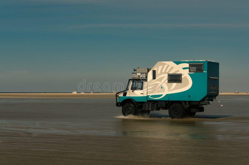 La autocaravana vadea el agua poco profunda por la playa fotografía de archivo libre de regalías
