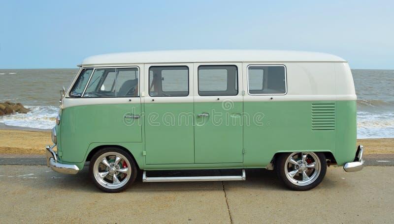 La autocaravana verde y blanca clásica de VW parqueó en la 'promenade' de la orilla del mar imagen de archivo