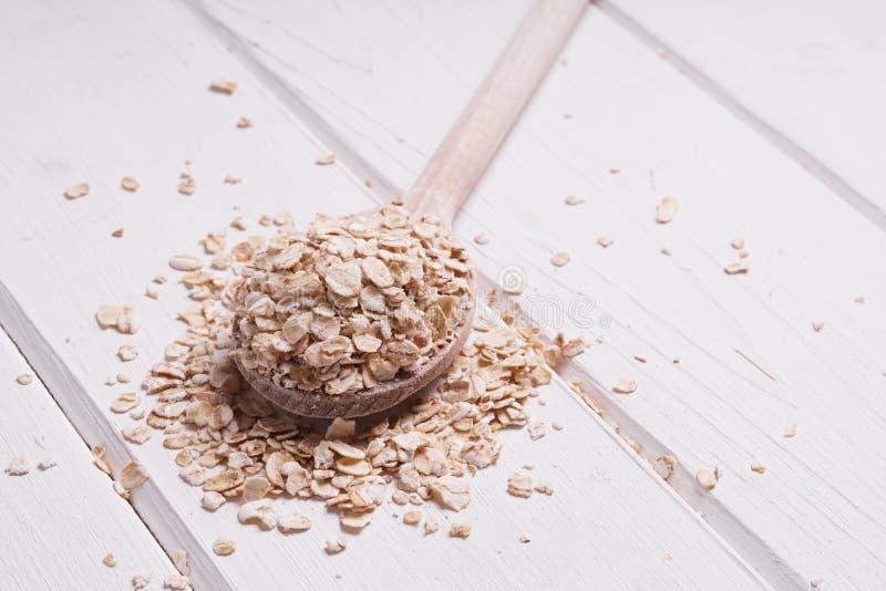 La avena de la harina de avena de la avena rodada forma escamas en la cuchara de madera fotografía de archivo libre de regalías