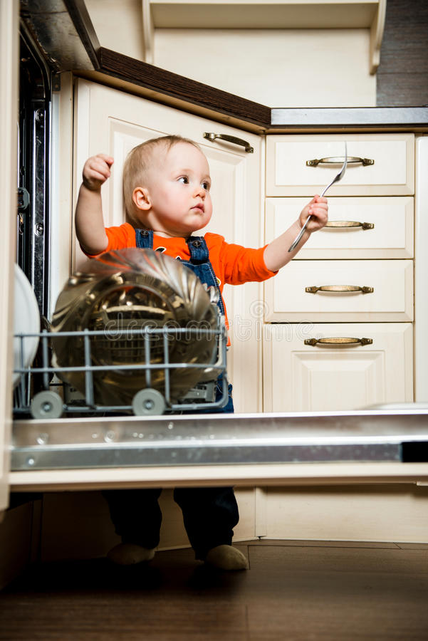 La ayuda del bebé descarga el lavaplatos fotografía de archivo libre de regalías