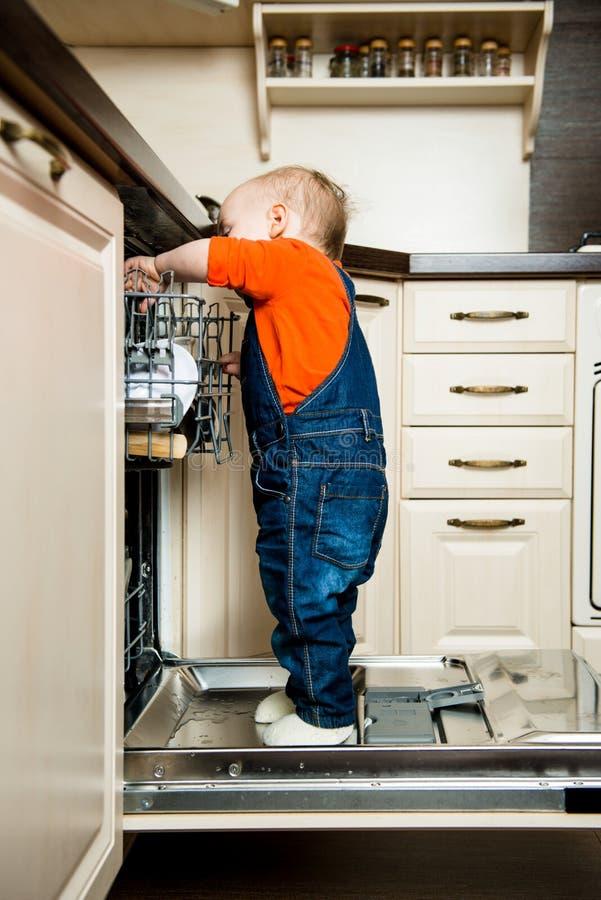 La ayuda del bebé descarga el lavaplatos fotos de archivo libres de regalías