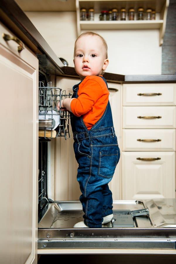 La ayuda del bebé descarga el lavaplatos imagen de archivo
