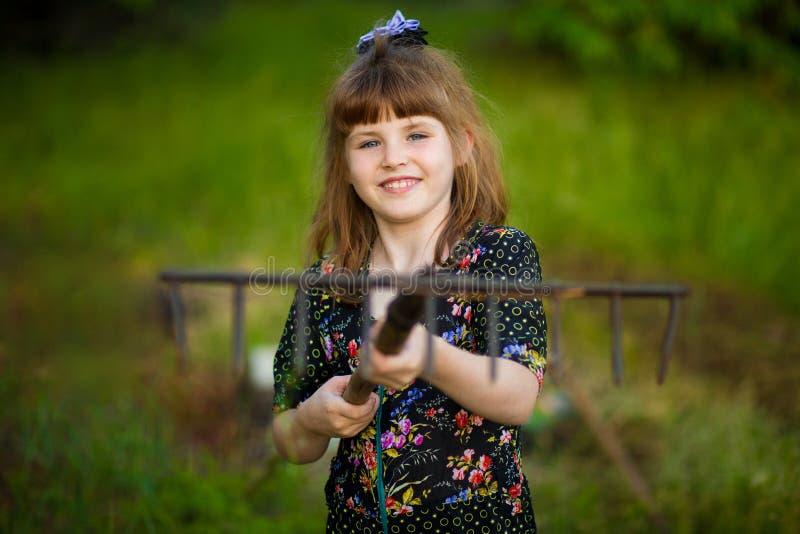La ayuda feliz de la niña parents en jardín con el rastrillo imagenes de archivo
