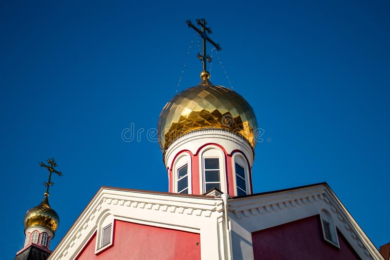 La bóveda dorada de la iglesia ortodoxa rusa con una cruz fotos de archivo