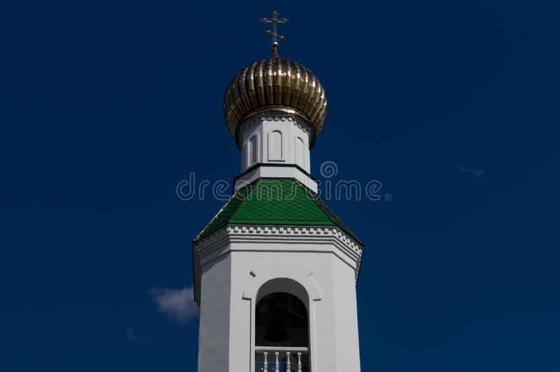 La bóveda dorada del campanario, la iglesia contra la perspectiva del cielo nublado imagenes de archivo