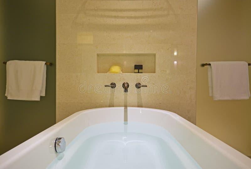 La bañera blanca llenada con el golpecito de cobre amarillo montó en la pared y las pantallas de ducha de mármol en ambos lados fotografía de archivo libre de regalías