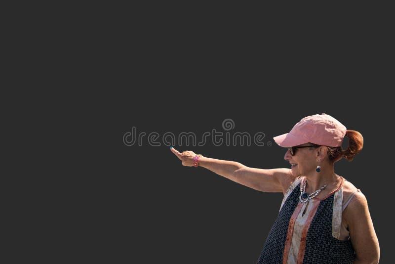 La baby boomer d'isolement de femme s'est habillée en passant avec le chapeau rose sur le gra photos stock