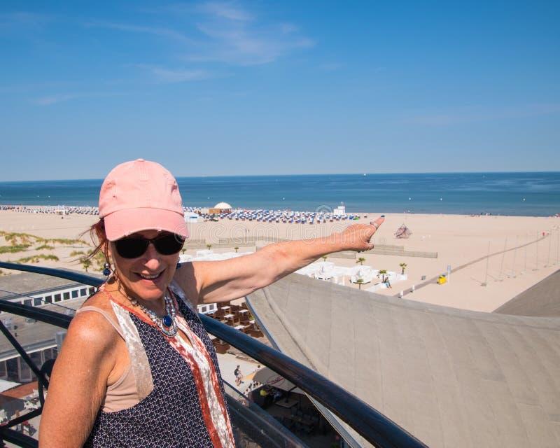 La baby boomer de sourire de femme s'est habillée en passant avec le chapeau rose sur le balc photos libres de droits