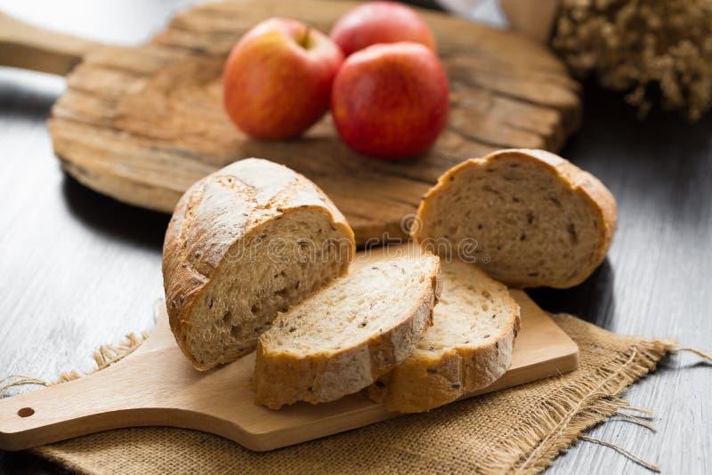 La baguette de pain français a coupé sur le conseil en bois avec le couteau avec un cho photos libres de droits