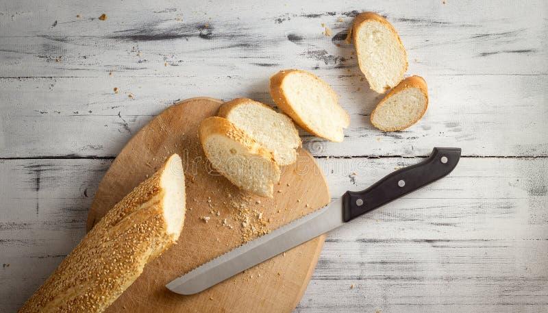 La baguette française a coupé avec un couteau sur la planche à découper images stock
