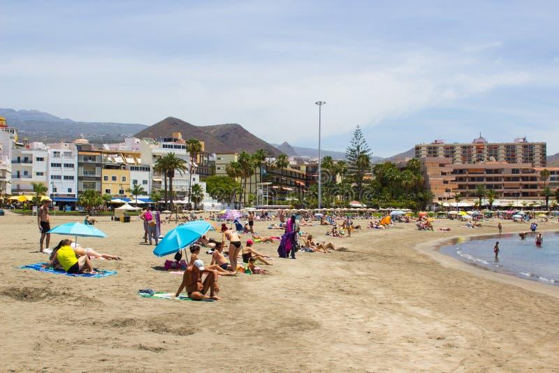 La bahía arenosa en Los Cristianos en Tenerife con el baño de sol de los fabricantes del día de fiesta y hoteles y montañas en el imagen de archivo libre de regalías