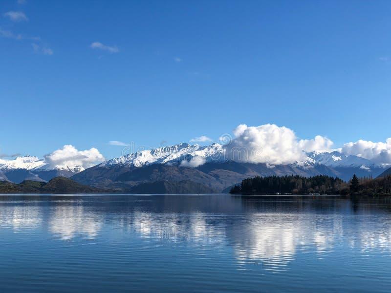 La bahía de Roys en Wanaka en Nueva Zelanda con nieve capsuló las montañas y las nubes en la visión imágenes de archivo libres de regalías