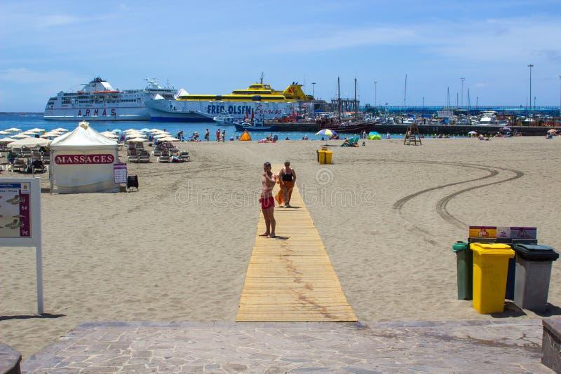 La bahía en y la terminal de transbordadores arenosas en Los Cristianos en Tenerife con la isla balsea en los fabricantes del pue foto de archivo