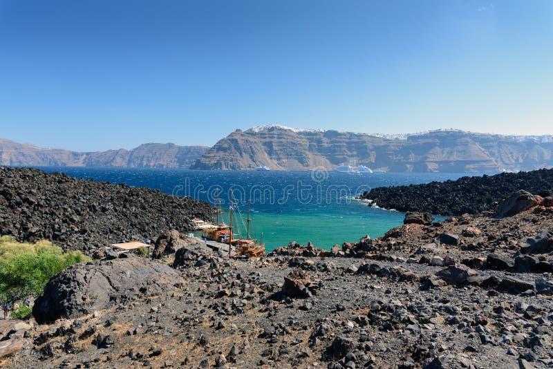 La baie de mer avec les bateaux amarrés s'approchent du volcan de l'île de Santorini, Grèce photo stock