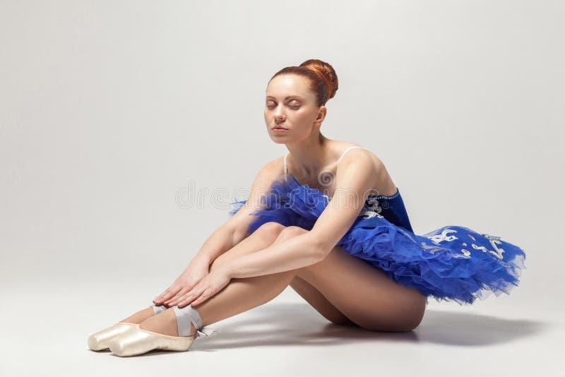 La bailarina con los ojos cerrados en vestido y pointe azules calza sittin fotografía de archivo libre de regalías