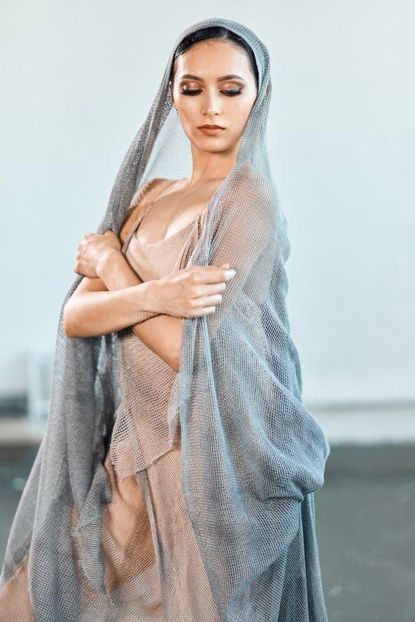 La bailarina con un cuerpo perfecto y un vestido rom?ntico de la red est? bailando en estudio imagen de archivo